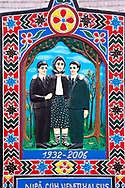 Tombstone of a mother showing her with her sons,  The  Merry Cemetery ( Cimitirul Vesel ),  Săpânţa, Maramares, Northern Transylvania, Romania.  The naive folk art style of the tombstones created by woodcarver  Stan Ioan Pătraş (1909 - 1977) who created in his lifetime over 700 colourfully painted wooden tombstones with small relief portrait carvings of the deceased or with scenes depicting them at work or play or surprisingly showing the violent accident that killed them. Each tombstone has an inscription about the person, sometimes a light hearted  limerick in Romanian. .<br /> <br /> Visit our ROMANIA HISTORIC PLACXES PHOTO COLLECTIONS for more photos to download or buy as wall art prints https://funkystock.photoshelter.com/gallery-collection/Pictures-Images-of-Romania-Photos-of-Romanian-Historic-Landmark-Sites/C00001TITiQwAdS8