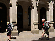 Just arriving the two elderly pilgrims walk through the arched streets of Santiago de Compostela. They were on their way to their accommodation.