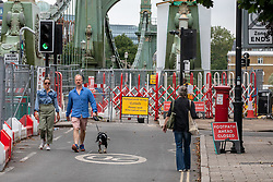 © Licensed to London News Pictures. 14/08/2020. London, UK. Walkers go around Hammersmith Bridge which crosses the River Thames in West London after Fulham Council suddenly closed it to all traffic Thursday night due to safety concerns. Hammersmith Bridge has been close to all traffic including pedestrians, cyclists and boats going under it after cracks in the bridge have become larger by the heatwave. Photo credit: Alex Lentati/LNP