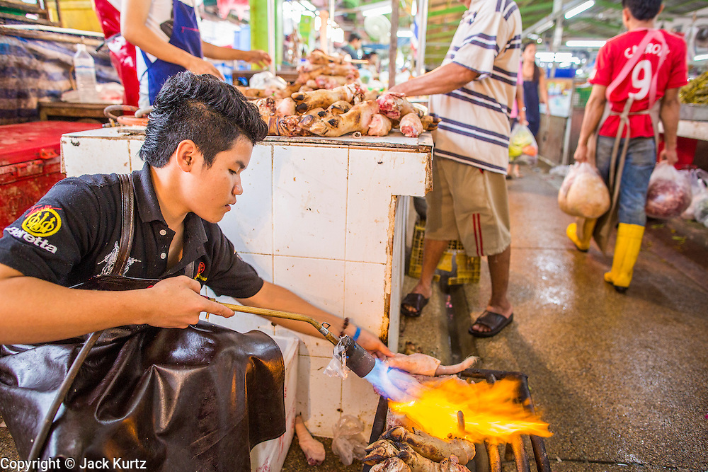 """03 OCTOBER 2012 - BANGKOK, THAILAND:     A worker burns hair off pig's feet in Khlong Toey Market in Bangkok. Khlong Toey (also called Khlong Toei) Market is one of the largest """"wet markets"""" in Thailand. Thousands of people shop in the sprawling market for fresh fruits and vegetables as well meat, fish and poultry every day.       PHOTO BY JACK KURTZ"""