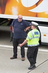 ©Licensed to London News Pictures 16/09/2020  <br /> Ashford, UK. Police officer talking to a trucker. The front of the queue of hundreds of lorries being held by police just before junction 9 on the M20.  There is freight chaos on the roads in Kent this afternoon as Operation Stack is implemented due to increased security checks at the Port of Dover and Eurotunnel. The M20 motorway is closed to cars between junction eight and nine so police can hold freight traffic. Photo credit:Grant Falvey/LNP