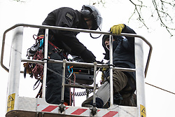 Steeple Claydon, UK. 23 February, 2021. An activist falls into a cherry picker after a National Eviction Team bailiff acting for HS2 Ltd cut his line during an operation to evict activists opposed to the HS2 high-speed rail link from ancient woodland known as Poors Piece. The activists created the Poors Piece Conservation Project there in spring 2020 after having been invited to stay on the land by its owner, farmer Clive Higgins. Already, local village communities have been hugely impacted by HS2, with 550 acres of land seized including a large section of a nature reserve.