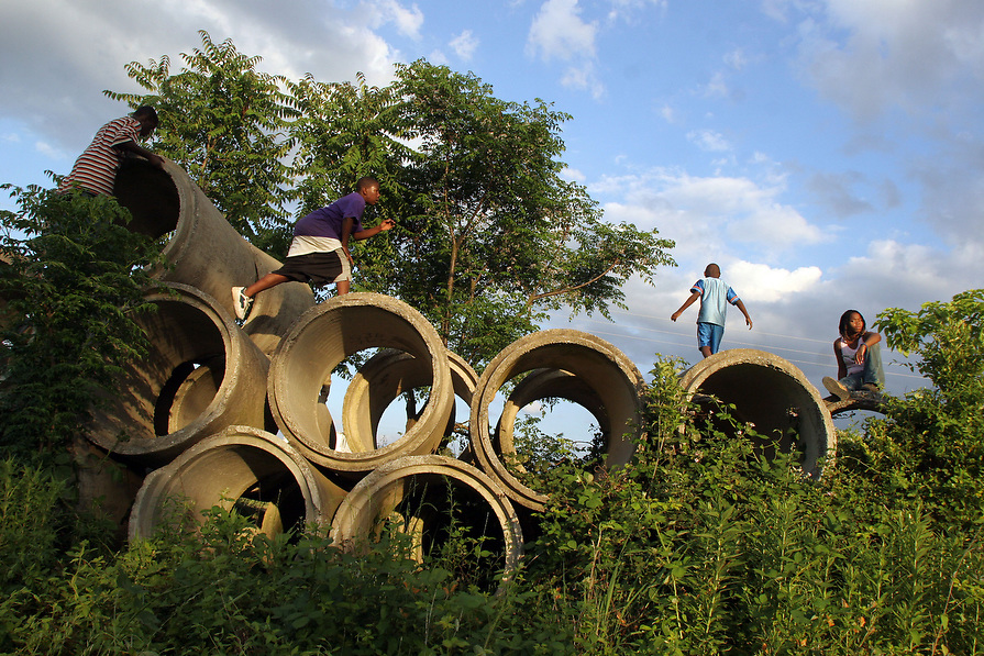 Mario Wright, left, Marvin Wright, Brandon Davis, and Marvina Wright use cement pipes as a playground, which is across the railroad tracks from the Wright's home.