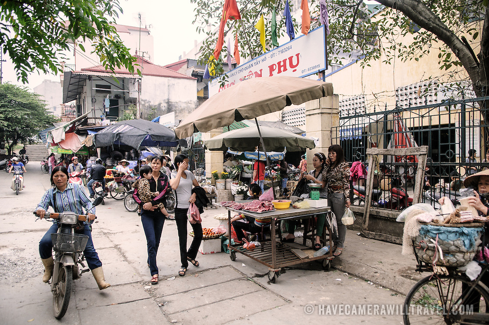 The bustling entrance of a morning market in Hanoi, Vietnam.