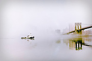 A tugboat passes by the Brooklyn Bridge on a foggy morning, as seen from the Empire Fulton Ferry Water Taxi Landing in Brooklyn, New York City, 2010.