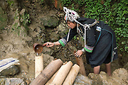 In the remote Akha Nuquie ethnic minority village of Ban Chakhampa, Phongsaly Province, Lao PDR, women's first task of the day is to collect water using a gourd scoop and carry it back to the village in traditional bamboo water carriers. One of the most ethnically diverse countries in Southeast Asia, Laos has 49 officially recognised ethnic groups although there are many more self-identified and sub groups. These groups are distinguished by their own customs, beliefs and rituals.