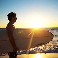 Guy with surfboard at Cottesloe Main Beach silhouette against the sunset
