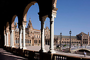 Looking up at the ornate arches and collonades of Seville's Plaza de Espana. The fine curves of this semi-circular is seen on a fine afternoon during Semana Santa (Easter Holy Week) anf the Torres (tower) of one end rises into a blue sky. This semi-circular enclosure was built by Aníbal González, the great architect of Sevillian regionalism, for the Ibero-American exposition held in 1929. It is a landmark example of the Renaissance Revival style in Spanish architecture. Today the Plaza de España mainly consists of Government buildings. The Seville Town Hall, with sensitive adaptive redesign, is located within it.
