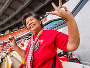 """19 NOVEMBER 2013 - BANGKOK, THAILAND: A Red Shirt supporter dances to Thai country music during a Red Shirt rally in Bangkok. As many as 30,000 """"Red Shirts"""" are expected in Bangkok this week ahead of a Thai court ruling that could cause the collapse of the government of Yingluck Shinawatra, the Prime Minister. The Red Shirts are gathering in a suburban sports stadium before marching to the court. The Red Shirts are mostly farmers and rural Thais who support the Shinawatra government.     PHOTO BY JACK KURTZ"""