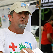 A volunteer named Sammy hands out registration forms and signature forms at the PUFFM booth during the Earthday Birthday Concert at the Citrus Bowl in Central Florida, to support legalizing medicinal marijuana use by a cancer patients. State residents, with the help of a group called United for Care, are urging backers to sign petitions to get the legalization of medicinal marijuana on the ballot for the early 2014 Florida legislative session. This image taken in Central Florida on Saturday, April 13, 2013. (Photo/Alex Menendez)