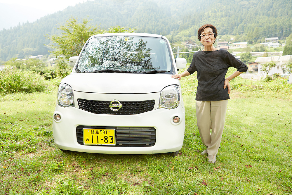 Lifestyle image of senior woman standing next to white car in countryside mountains in Far East Asia