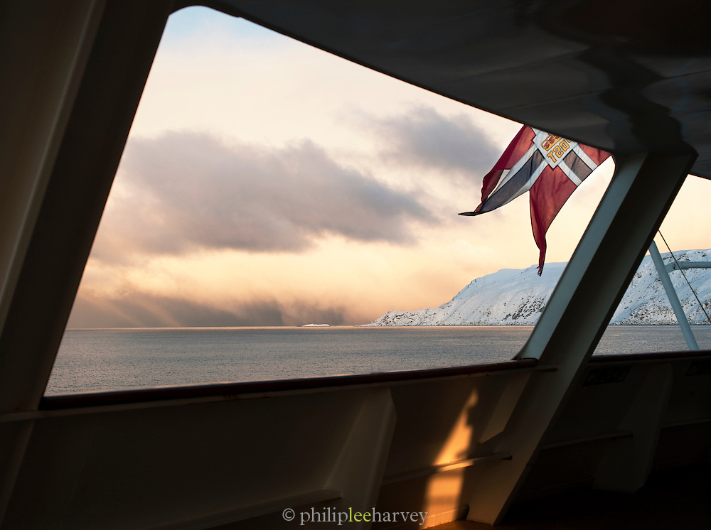 View of snowy landscapes of Finnmark region, seen from the stern of a cruise ship at sea, northern Norway
