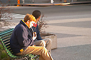 Two young men on a park bench drinking mate herbal tea from a cup on the Plaza Independencia Independence Square Montevideo, Uruguay, South America
