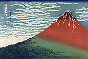Mount Fuji in a Clear Dawn. From 'Thirty-six Views of Mount Fuji', c1831. Katsushika Hokusai (1760-1849) Japanese  Ukiyo-e artist. Mountain rising from wooded slope to red peak against white clouds in blue sky. Landscape
