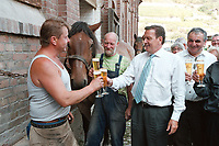 24 AUG 2000, NAUMBURG/GERMANY:<br /> Gerhard Schroeder, SPD, Bundeskanzler, trinkt ein Bier, mit einem Hufschmied, einen Kutscher, und dessen frisch beschlagenen Kaltblutpferd, auf einem Gehoeft in der Naehe von Naumburg, Sommerreise des Kanzlers durch die Ostdeutschen Bundeslaender<br /> IMAGE: 20000824-01/03-24<br /> KEYWORDS: Gerhard Schröder, Pferd, Tier, horse, animal, Hufeisen, Handwerk, Arbeit, work, beer, Alkohol, alcohol, Getraenk, drink