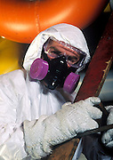 Asbestos removal worker with protective suit and mask at a industrial site.
