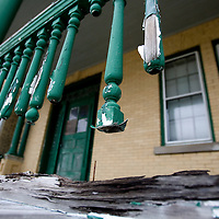 A dilapidated railing with peeling paint and missing rungs on a building in Fort Hancock at Sandy Hook known to many as officers row.  Fort Hancock itself is a former United States Army fort located at Sandy Hook along the Atlantic coast of eastern New Jersey in the United States. This coastal artillery base played an important part in the defense of New York Harbor and played a role in the History of New Jersey.
