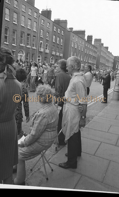 Women's Peace March In Dublin  (K50)..1976..28.08.1976..08.28.1976..28th August 1976..As part of the Peace Movement, set up by Ms Betty Williams and Ms Mairead Maguire in Northern Ireland, a march was organised for Dublin. Thousands of women took part in the march from St Stephen's Green, Dublin to the seat of government in Leinster House on Merrion Square, Dublin, to protest the continuing violence within the country..Image taken as one lady takes a rest as the peace march passes along Merrion Street, Dublin.