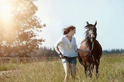 Young woman running with her brown horse on meadow and smiling, Bavaria, Germany