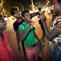 Kavia, an Aravani shares a cigarette with some boys while she looks for sex works on the streets of  Chennai...India's transexual community has a recorded history of more than four thousand years. Many consider the The Third Sex, also known as Aravanis, to posses special powers allowing them to determine the fate of others. As such, they are not only revered but despised and feared too. Resigned to the fringes of society, segregated and excluded from most occupations, many Aravanis are forced to turn to begging and sex work in order to earn a living. ..The annual transgender festival in the village of Koovagam, near Vilappuram, offers an escape from this often desolate existence. For some, the week-long partying and frenetic sex trade that culminates in the Koovagam festival is about fulfilling lustful desires. For others, the gathering provides a chance for transgenders to bond, share experiences, join the wider homosexual gay-community and coordinate their campaign for recognition and tackle the challenge of HIV/AIDS. ..It is the Indian state of Tamil Nadu that the eighty-thousand-strong Aravani community has made advances in their fight for rights. In 2009, the Tamil Nadu state government began providing sex-change surgery free of cost. The state has also offers special third-gender ration cards, passports and reserved seats in colleges. And 2008 the launch of Ippudikku Rose, a Tamil talk-show fronted by India's first transgender TV-host and the release of a mainstream Tamil film staring an Aravani in the lead-role. ..These advances clearly signal a victory for south India's transgenders, but they have also exposed deep divisions within the community. There is a very real gulf that separates the majority poor from their potentially influential but often reticent, upper-class sisters. ..Photo: Tom Pietrasik.Chennai, Tamil Nadu. India.May 2009
