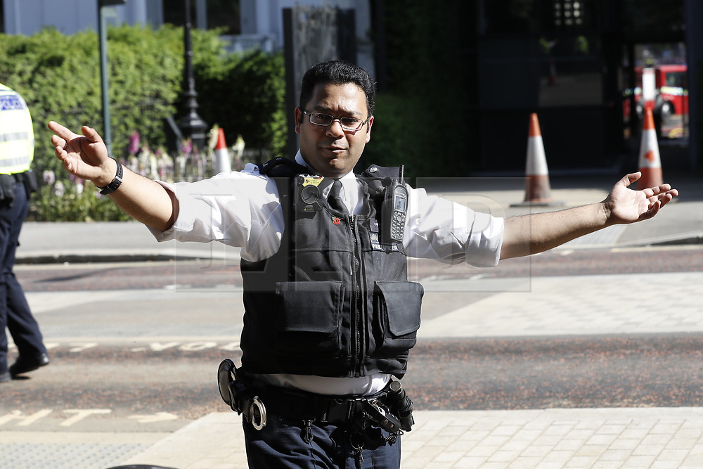 © Licensed to London News Pictures. 06/06/2018. London, UK. A policeman shouts at people to move away from the Mandarin Oriental hotel during a fire. Fifteen fire engines and 97 firefighters and officers have been called to a fire believed to be at the Mandarin Hotel in Kightsbridge. Photo credit: Peter Macdiarmid/LNP
