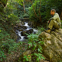 Hiker resting at the Mae Surin waterfall at the Mae Surin National Park in Mae Hong Son, Thailand.