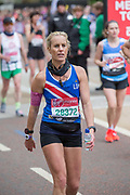 A tired female participant walking the last 600 metres of The Virgin London Marathon at Birdcage Walk on 28th April 2019 in London in the United Kingdom. Now in it's 39th year, the London Marathon is a large sporting event with over 40,000 runners expected to take part.