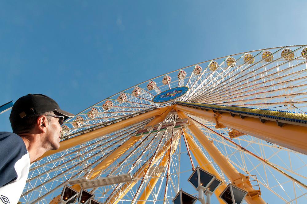 Ein Mann im mittleren Alters aus einem arabischen Land Nordafrikas  blickt auf ein Riesenrad  in dessen Mitte sich die Fahnen der europäischen Union  befinden   |  A man of an north-african  arabian  country stares at the flaggs of the european Union on a big wheel