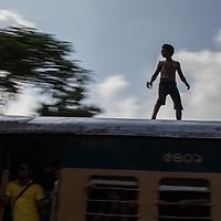 A boy rides on top of a train in Dhaka, Bangladesh
