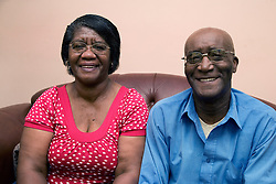Older couple sitting on the sofa smiling,