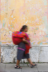 Mayan woman walking in front of colorful, painted wall, Antigua, Guatemala