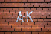 The stencilled letters A-K sprayed on to a brick wall of a modern development in the north London of Kings Cross.