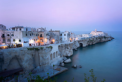 Traditional houses on a cliff on the Mediterranean sea at sunset, Apulia, Italy