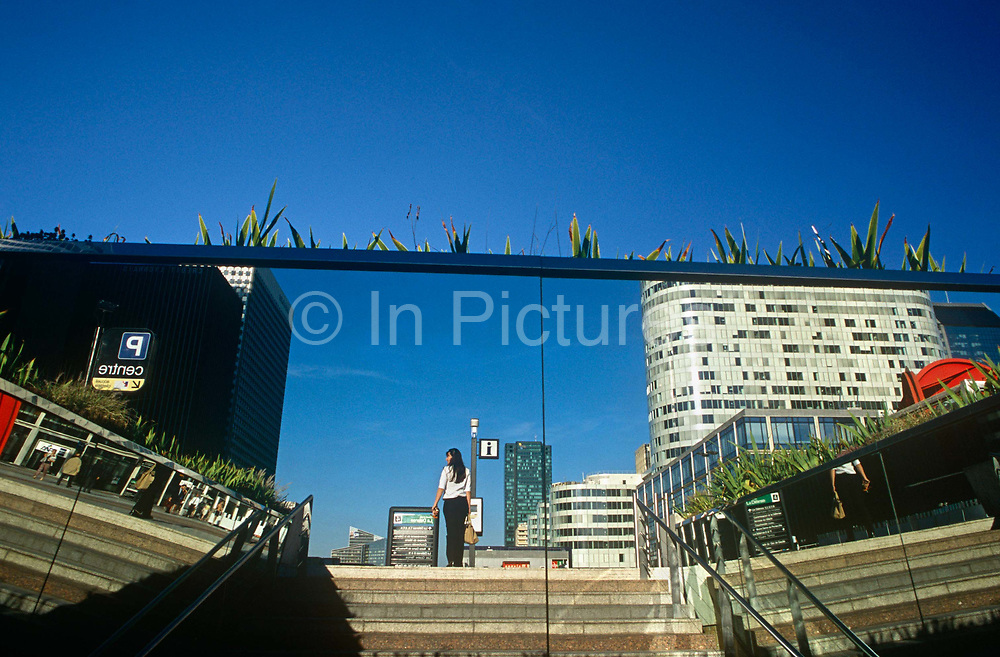 Amid the deep blue skies of a summer landscape in the city, a lone figure of a woman is reflected in a large mirror as she walks through La Defence in central Paris. Reflected in a large, polished mirror we see the lone female with her back turned to us as she looks over her left shoulder. In front of her is an information post but apart from a pair of legs from an unseen passer-by, she is alone in this busy financial district of the French capital. La Défense is a major business district of the Paris aire urbaine. With a population of 20,000,[1] it is centered in an orbital motorway straddling the Hauts-de-Seine département municipalities of Nanterre, Courbevoie and Puteaux. The district is at the westernmost extremity of Paris's 10km long Historical Axis