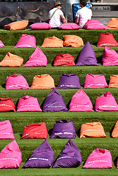 © Licensed to London News Pictures. 03/07/2018. LONDON, UK.  Brightly coloured beanbags are set out on the steps by Granary Square for people to enjoy the current sunshine and hot weather as well as to watch coverage of tennis from Wimbledon on a nearby big TV screen.  The Championships 2018 at Wimbledon commenced 2 July and will run for two weeks.  Photo credit: Stephen Chung/LNP