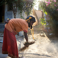 """Vijyashree Viswanathan (age 11) cleans the area outside the home she shares with her father and his new wife in the fishing village of Thazanguda, near Cuddalore. ..Vijita (age 14) and Vijyashree (age 11) Viswanathan lost their mother and brother to the tsunami in 2004. They continue to live in the fishing village of Thazanguda with their father Viswanathan, his second wife Kayalvizhi and their two children Sanjay (age 3) and Monica (age 1). ..Until the beginning of the 2009 academic year in June, Vijita and Vijyashree attended the local Thazanguda school. This village school teaches pupils only until the 8th Standard and with Vijita now entering the 9th, it was decided that the two daughters remain together and both travel 3km to the local town school: the Government Girls High School, Venugopalapuram in Cuddalore. ..At the same time Viswanathan decided he would cease day-to-day care of his daughters and place them in the Government Home for Tsunami Children, also in Cuddalore. This was not a move welcomed by either Vijita or Vijyashree and one afternoon after just two weeks at the orphanage, the two girls ran away. At roll call in the orphanage that evening the alarm was sounded and the two sisters were eventually located in Thazanguda waiting for their father and Kayalvizhi who were both away at the time. Realising his daughters' unhappiness, Viswanathan then took them out of the Government home. ..According to her class teacher, Vijita often compares her step-mother to her mother and concludes that she wants her mother back. Vijita confides in her teachers that her stepmother is forever demanding that she and her sister Vijyashree undertake housework. This frustration at home is tempered by the genuine love both sisters have for their father and two younger siblings Sanjay and Monica. Vijita expresses a lonelyness without her mother. Pushpavalli concludes that """"Vijita wants something else beyond the love of her father and sister"""". ..Viswanathan appears genuinely"""