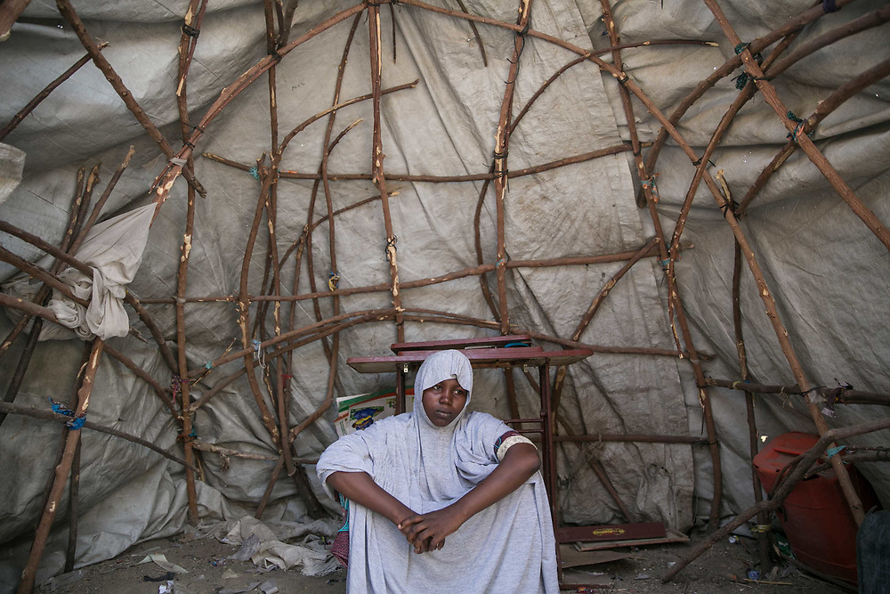 Yagana, 23, sits in her empty makeshift tent after she removed all her belongings as a robber had come in and stole seven fabrics in an IDP camp in Maiduguri, Nigeria, April 30, 2019. Yagana was abducted by four Boko Haram fighters in Mafa Local Government in 2014 and taken to the Sambisa Forest. When the Nigerian Military attacked their hideout in 2015, she was rescued by the army and gave birth to a baby in the military detention center in Giwa. As she was forced to leave the secondary school by BH, she wanted to continue her education and took a graduation exam on April 26, 2019.