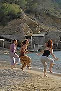 People enjoying sundays in popular Benirras beach, where drum players play until sunset, Ibiza, Spain