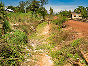 03 JUNE 2016 - SIEM REAP, CAMBODIA: An empty irrigation canal in Sot Nikum, a village northeast of Siem Reap. Wells in the village have been dry for more than three months because of the drought that is gripping most of Southeast Asia. People in the community rely on water they have to buy from water sellers or water brought in by NGOs. They were waiting for water brought in by truck from Siem Reap by Water on Wheels, a NGO in Siem Reap. Cambodia is in the second year of  a record shattering drought, brought on by climate change and the El Niño weather pattern. There is no water to irrigate the farm fields and many of the wells in the area have run dry.     PHOTO BY JACK KURTZ