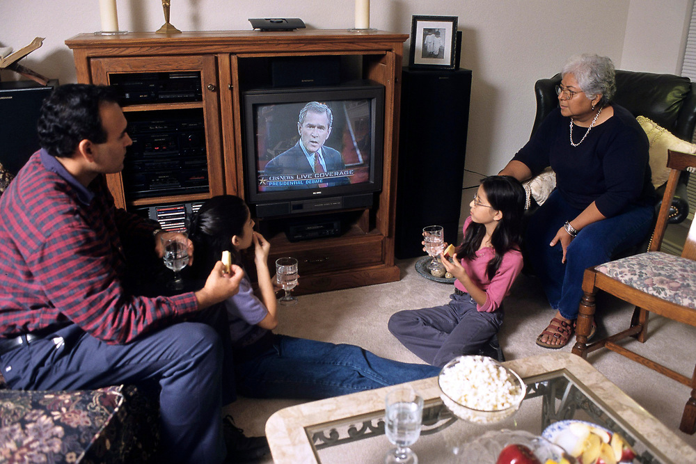 Hispanic family watching Presidential canidates debate on TV at home in living room.  MR .©Bob Daemmrich
