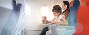 photographie en couleur d'un enfant qui dessine tranquillement à bord d'un avion de la compagnie aérienne Aircalin Nouvelle Calédonie en vol.