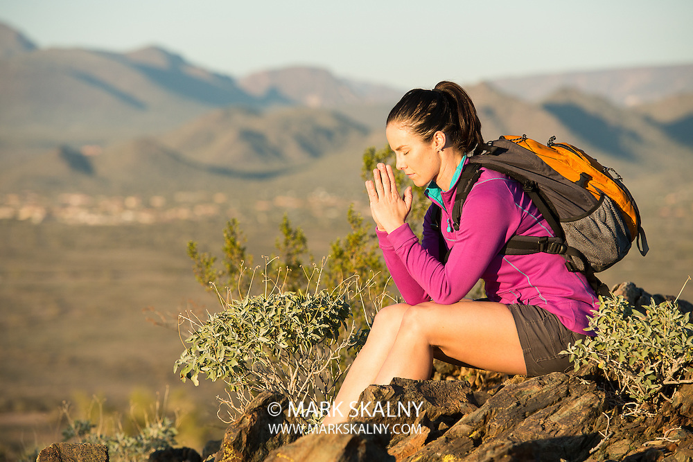Young woman pauses at the top of a trail midway through her hike at Phoenix Sonoran Preserve in Phoenix, Arizona. She is taking a moment to self reflect.