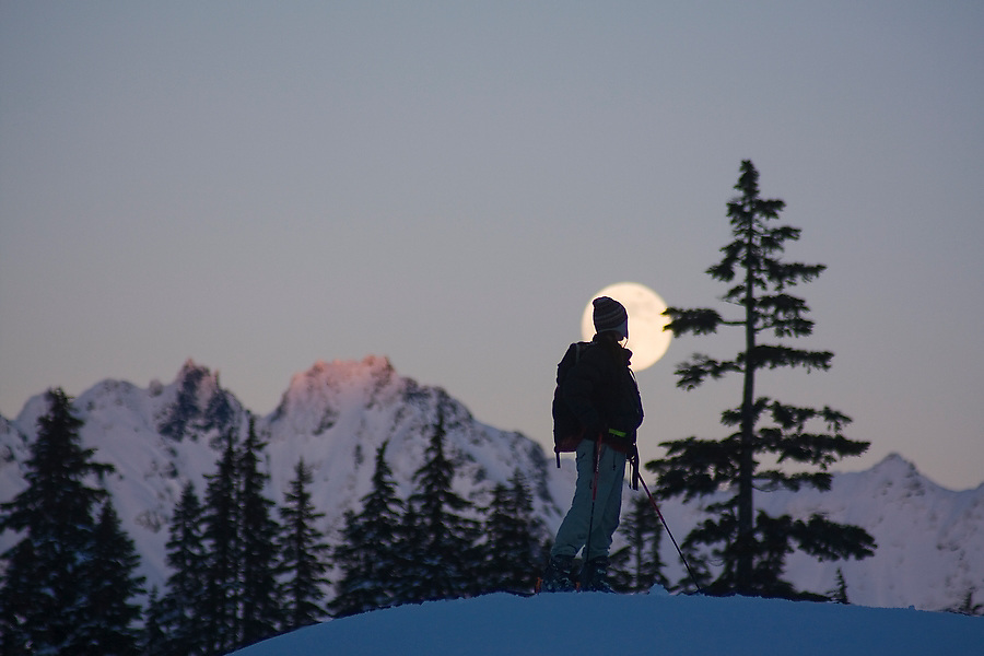 A lone skier watches the moon rise over the Cascades at sunset during a ski tour in the Mount Baker backcountry, Washington.