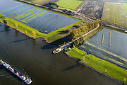 Nederland, Brabant, Gemeente Waspik, 28-10-2013; Overdiepsche polder met veerpont naar Dussen. In het kader van het programma 'Ruimte voor de Rivier' (bescherming tegen hoogwater door rivierverruiming), is de zomerdijk langs de Bergsche Maas van instroomgaten voorzien, terwijl de winterdijk verlaagd wordt. De uiterwaarden zijn overstroomd, bij hoogwater kan de Overdiepse polder ook overstromen. <br /> Depoldering of Overdiep Polder, farms are relocated and built on mounds. This makes it possible for the river to overflow the polder in case of heigh waters. The dikes have been excavated.<br /> luchtfoto (toeslag op standard tarieven);<br /> aerial photo (additional fee required);<br /> copyright foto/photo Siebe Swart
