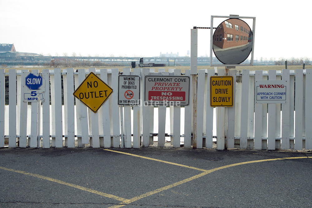 in the bent of a residential road many traffic and warning signs on a wooden fence