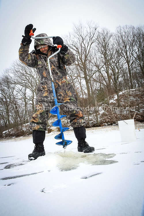 (1/10/14, HOPKINTON, MA) Dan Schrag of Framingham drills a fresh hole in the ice to set an ice fishing trap at Hopkinton State Park on Friday. Daily News and Wicked Local Photo/Dan Holmes
