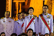 05 DECEMBER 2013 - BANGKOK, THAILAND: YINGLUCK SHINAWATRA (center) the Prime Minister of Thailand, and ANUSORN AMORNCHAT, her husband, (right) on stage the celebration of the birthday of the King in Bangkok. Thais observed the 86th birthday of Bhumibol Adulyadej, the King of Thailand, their revered King on Thursday. They held candlelight services throughout the country. The political protests that have gripped Bangkok were on hold for the day, although protestors did hold their own observances of the holiday. Thousands of people attended the government celebration of the day on Sanam Luang, the large public space next to the Grand Palace in Bangkok.     PHOTO BY JACK KURTZ
