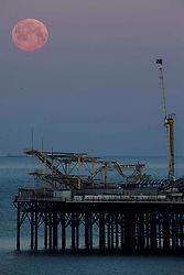 © Licensed to London News Pictures.  27/04/2021. Brighton, UK. The supermoon also known as Pink Moon goes down above Brighton Pier in East Sussex. A supermoon is a full moon or a new moon that nearly coincides with perigee--the closest that the Moon comes to the Earth. Photo credit: Marcin Nowak/LNP