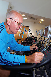 Disabled elderly man with impaired vision using new gym facilities especially adapted for disabled access to keep fit & healthy Yorkshire UK