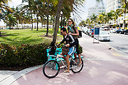 Young couple sharing a bicycle on Ocean Drive, South Beach, Miami, Florida, USA